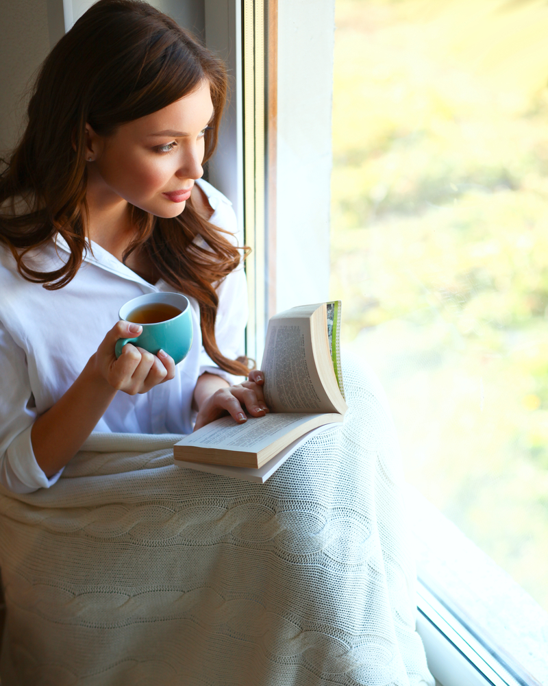 Young woman at home sitting near window relaxing in her living room reading book and drinking coffee or tea.