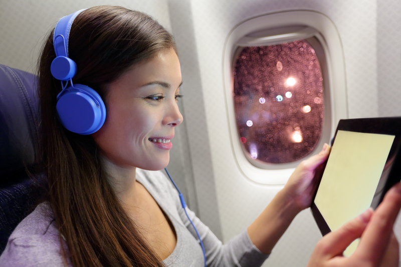Passenger in airplane using tablet computer