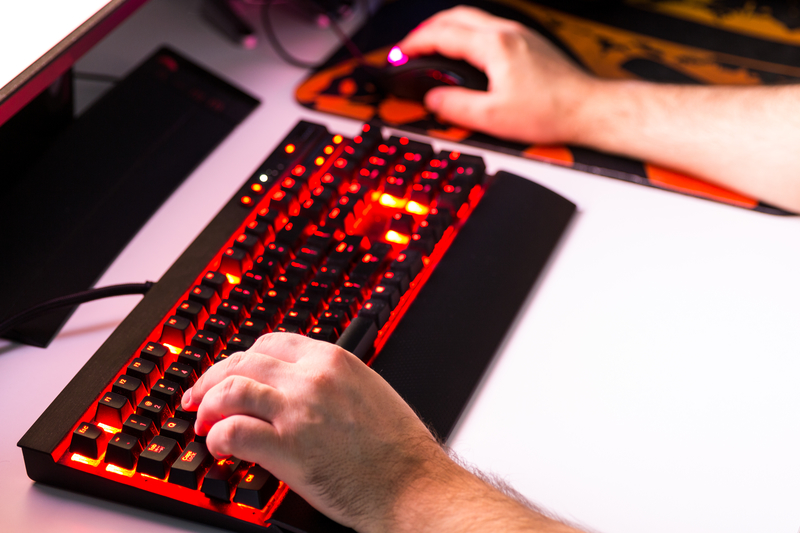 Man playing computer game on custom made desktop with joypad, ke