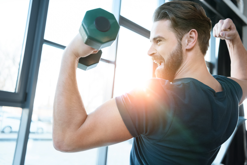 Handsome young guy workout with dumbbell
